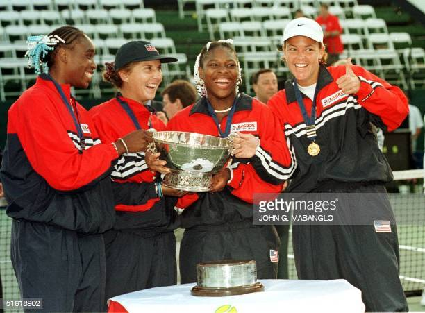 Lindsay Davenport gives a thumbs up as teammates Venus Williams Monica Seles and Serena Williams of the USA pose after receiving the Fed Cup trophy...