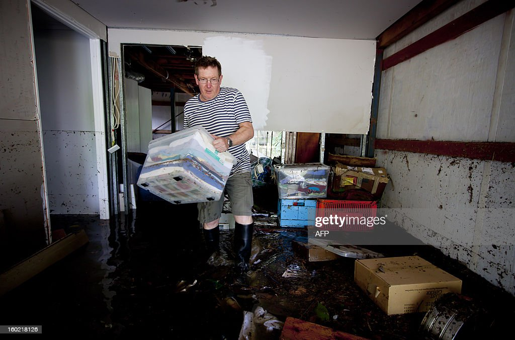 Lindsay Enright starts the clean up in the flooded area of his Cullen Street home, in the inner Brisbane suburb of Newmarket on January 28, 2013. Helicopters plucked dozens of stranded Australians to safety in dramatic rooftop rescues on January 28 as severe floods swept the northeast, killing three people and inundating thousands of homes. AFP PHOTO / Patrick HAMILTON