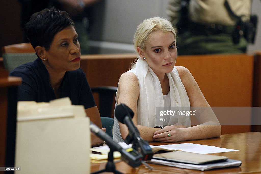 <a gi-track='captionPersonalityLinkClicked' href=/galleries/search?phrase=Lindsay+Lohan&family=editorial&specificpeople=171623 ng-click='$event.stopPropagation()'>Lindsay Lohan</a> attends her probation progress report hearing with her lawyer <a gi-track='captionPersonalityLinkClicked' href=/galleries/search?phrase=Shawn+Chapman+Holley&family=editorial&specificpeople=5763122 ng-click='$event.stopPropagation()'>Shawn Chapman Holley</a> at (L) the Airport Courthouse on October 19, 2011 in Los Angeles, California. Judge Stephanie Sautner suspended Lohan's probation and bail has been set at USD 100,0000 after Lohan was terminated by the Downtown Women's Center for repeatedly failing to appear for community service. If Lohan posts bail she has been ordered to community service for 16 hours per week at the L.A. County coroner's office until her next court date on November 2. Lohan has been sentenced to a total of 480 hours of community service stemming from a 2007 drunk-driving conviction and a jewelry theft conviction earlier this year.