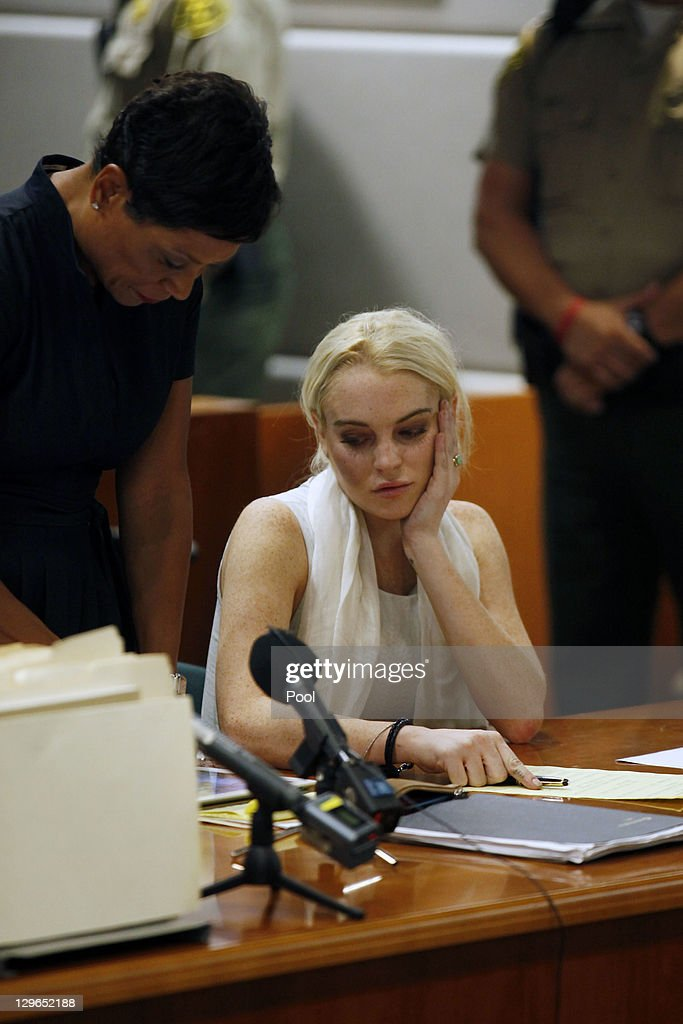 <a gi-track='captionPersonalityLinkClicked' href=/galleries/search?phrase=Lindsay+Lohan&family=editorial&specificpeople=171623 ng-click='$event.stopPropagation()'>Lindsay Lohan</a> attends her probation progress report hearing with her lawyer Shawn Chapman Holley at (L) the Airport Courthouse on October 19, 2011 in Los Angeles, California. Judge Stephanie Sautner suspended Lohan's probation and bail has been set at USD 100,000 after Lohan was terminated by the Downtown Women's Center for repeatedly failing to appear for community service. If Lohan posts bail she has been ordered to community service for 16 hours per week at the L.A. County coroner's office until her next court date on November 2. Lohan has been sentenced to a total of 480 hours of community service stemming from a 2007 drunk-driving conviction and a jewelry theft conviction earlier this year.