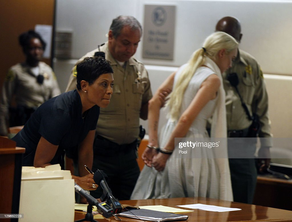 <a gi-track='captionPersonalityLinkClicked' href=/galleries/search?phrase=Lindsay+Lohan&family=editorial&specificpeople=171623 ng-click='$event.stopPropagation()'>Lindsay Lohan</a> is led away in handcuffs at her probation progress report hearing as her lawyer <a gi-track='captionPersonalityLinkClicked' href=/galleries/search?phrase=Shawn+Chapman+Holley&family=editorial&specificpeople=5763122 ng-click='$event.stopPropagation()'>Shawn Chapman Holley</a> (L) stands by at the Airport Courthouse on October 19, 2011 in Los Angeles, California. Judge Stephanie Sautner suspended Lohan's probation and bail has been set at USD 100,000 after Lohan was terminated by the Downtown Women's Center for repeatedly failing to appear for community service. If Lohan posts bail she has been ordered to community service for 16 hours per week at the L.A. County coroner's office until her next court date on November 2. Lohan has been sentenced to a total of 480 hours of community service stemming from a 2007 drunk-driving conviction and a jewelry theft conviction earlier this year.