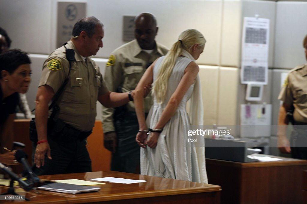 <a gi-track='captionPersonalityLinkClicked' href=/galleries/search?phrase=Lindsay+Lohan&family=editorial&specificpeople=171623 ng-click='$event.stopPropagation()'>Lindsay Lohan</a> is led away in handcuffs at her probation progress report hearing as her lawyer Shawn Chapman Holley (L) stands by at the Airport Courthouse on October 19, 2011 in Los Angeles, California. Judge Stephanie Sautner suspended Lohan's probation and bail has been set at USD 100,0000 after Lohan was terminated by the Downtown Women's Center for repeatedly failing to appear for community service. If Lohan posts bail she has been ordered to community service for 16 hours per week at the L.A. County coroner's office until her next court date on November 2. Lohan has been sentenced to a total of 480 hours of community service stemming from a 2007 drunk-driving conviction and a jewelry theft conviction earlier this year.