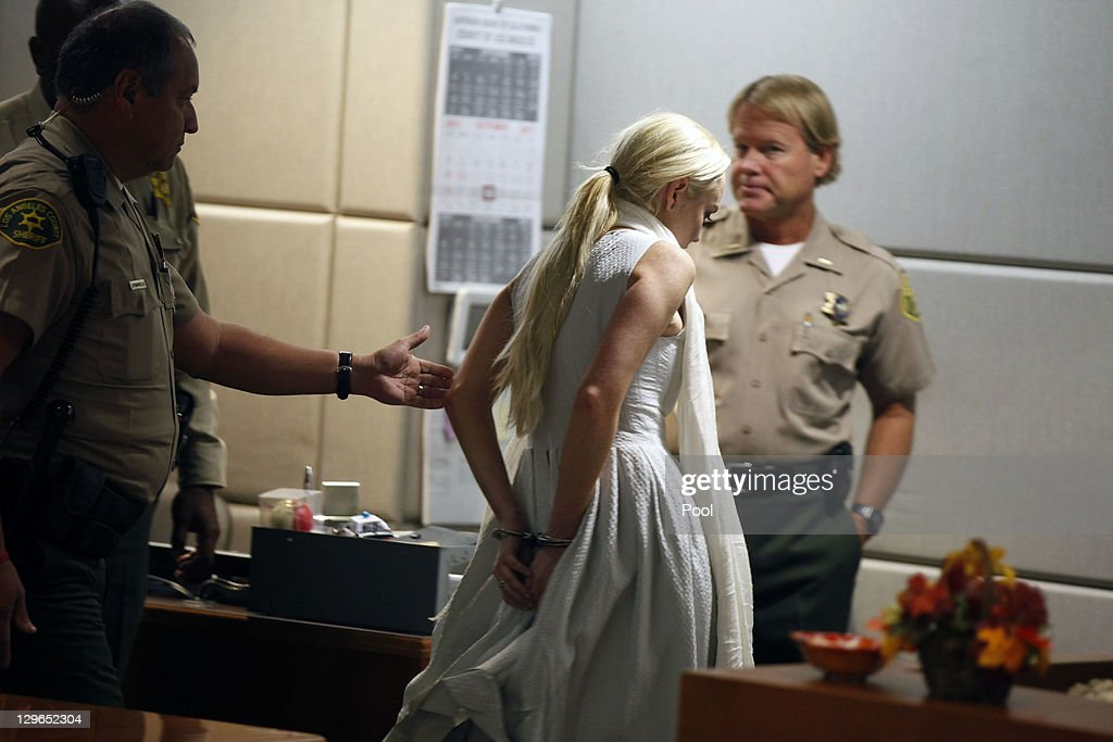 <a gi-track='captionPersonalityLinkClicked' href=/galleries/search?phrase=Lindsay+Lohan&family=editorial&specificpeople=171623 ng-click='$event.stopPropagation()'>Lindsay Lohan</a> is led away in handcuffs at her probation progress report hearing at the Airport Courthouse on October 19, 2011 in Los Angeles, California. Judge Stephanie Sautner suspended Lohan's probation and bail has been set at USD 100,0000 after Lohan was terminated by the Downtown Women's Center for repeatedly failing to appear for community service. If Lohan posts bail she has been ordered to community service for 16 hours per week at the L.A. County coroner's office until her next court date on November 2. Lohan has been sentenced to a total of 480 hours of community service stemming from a 2007 drunk-driving conviction and a jewelry theft conviction earlier this year.