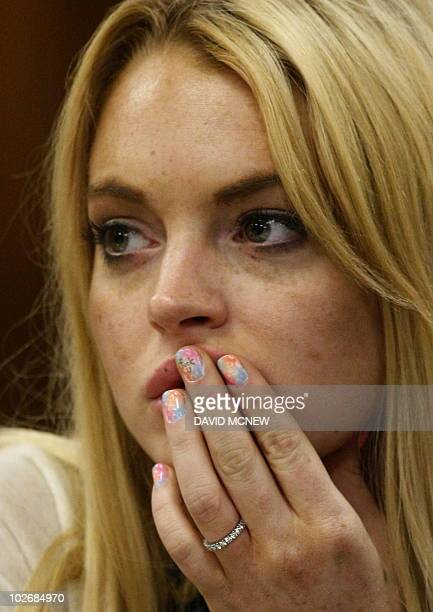 Lindsay Lohan sits with a message written on her fingernail before she is sentanced to 90 days jail by Judge Marsha Revel during her hearing at the...