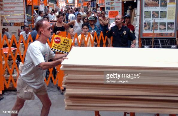 Lindsay Rogerson takes his share of plywood after waiting in line 6 hours in preparation for Hurricane Frances at a Home Depot on September 1 2004 in...