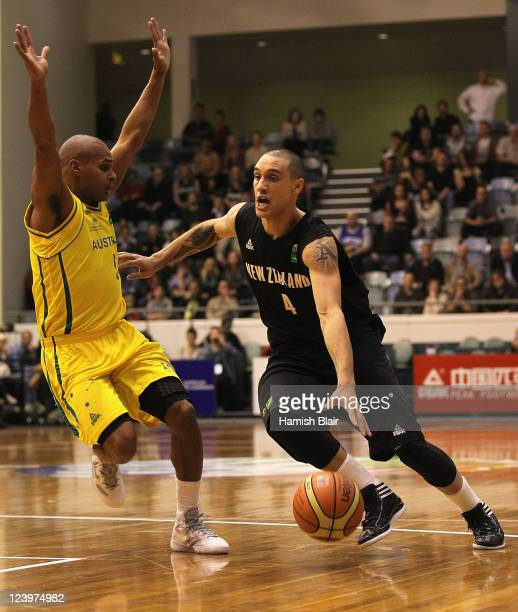 Lindsay Tait of New Zealand contests with Patrick Mills of Australia during the first match between the Australian Boomers and the New Zealand Tall...