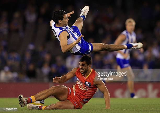 Lindsay Thomas of the Kangaroos collides with Karmichael Hunt of the Suns in a marking contest during the round five AFL match between the North...