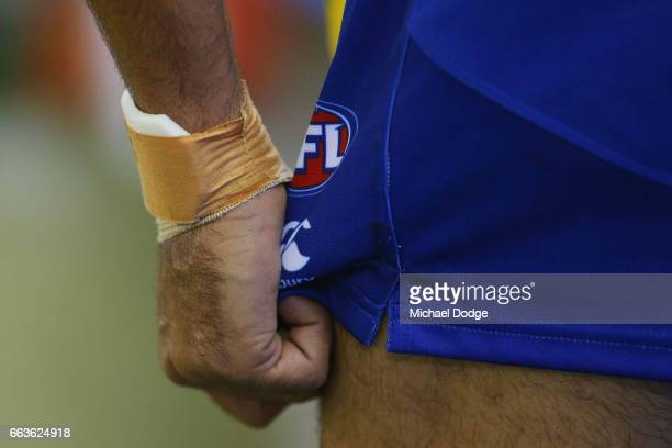 Lindsay Thomas of the Kangaroos grabs his shorts before kicking for goal during the round two AFL match between the Geelong Cats and the North...