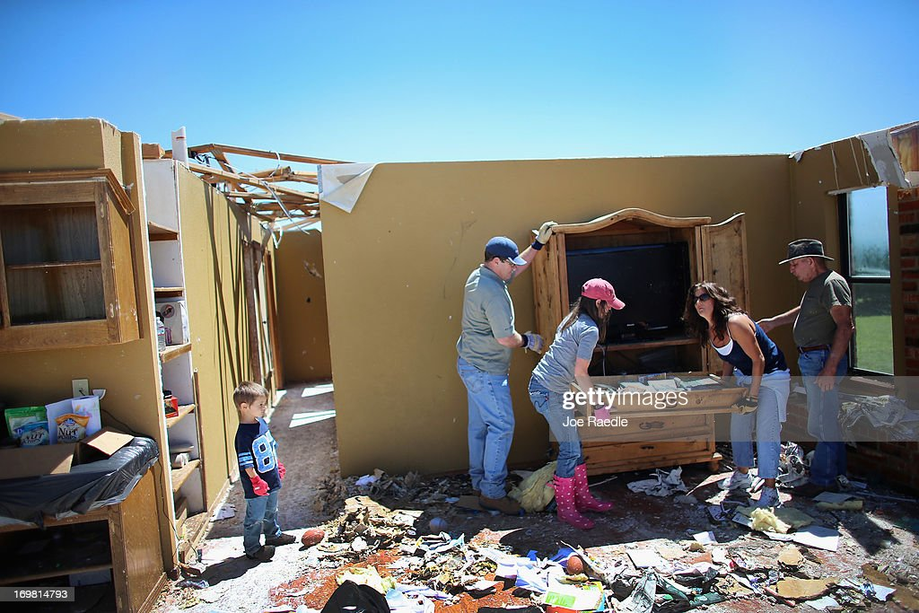 Lindsay Welton and Dana Givens take a drawer full of items from an armoire as they salvage what they can from a relatives home after it was destroyed by a tornado on June 2, 2013 in El Reno, Oklahoma. The tornado ripped through the area friday killing at least 9 people, injuring many and destroying homes and buildings.