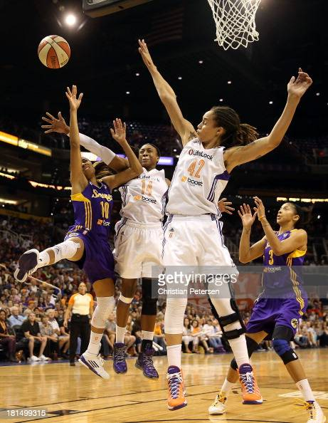Lindsey Harding of the Los Angeles Sparks is fouled as she attempts a shot against Alexis Hornbuckle and Brittney Griner of the Phoenix Mercury...