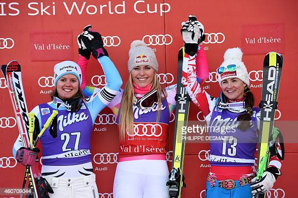 US Lindsey Vonn celebrates on the podium flanked by Austria's Elisabeth Goergl and Germany's Viktoria Rebensburg tied for the silver medal after...