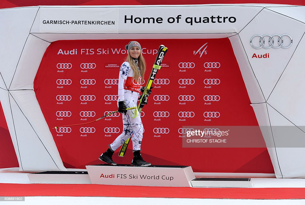 Lindsey Vonn from USA changes the podium position during the winner ceremony of the Ladies Super G competition race at the FIS Alpine Skiing World Cup in Garmisch-Partenkirchen, southern Germany, on February 7, 2016. Lara Gut from Switzerland won the competition, Viktoria Rebensburg from Germany placed second and Lindsey Vonn from USA placed third. / AFP / Christof STACHE