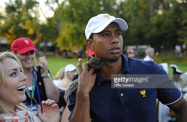 Lindsey Vonn places a baby squirrel on the shoulder of Tiger Woods of the US Team during the Day One FourBall Matches of The Presidents Cup at the...