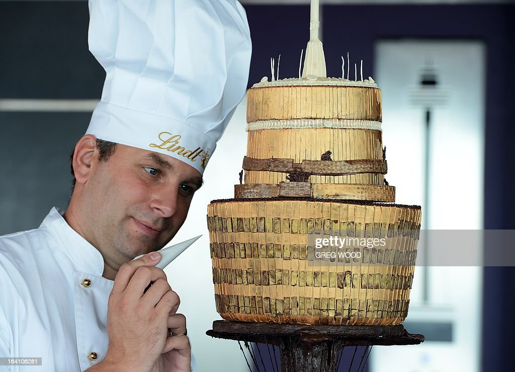 Lindt master chocolatier Thomas Schnetzler puts the finishing touches to a chocolate replica of the iconic Sydney Tower on the observation deck of the tower on March 20, 2013. In celebration of easter Schnetzler has spent over 40 hours hand-crafting the intricate tower which boasts over 300 windows and contains 12.5 kg's of dark chocolate with a coating of fine edible gold spray. AFP PHOTO / Greg WOOD