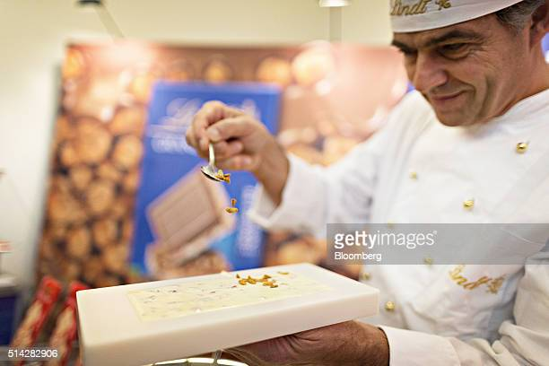 A Lindt Spugneli AG chocolatier sprinkles nuts into a white chocolate bar mould during a news conference to announce the company's full year results...
