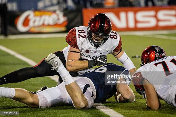 Line backer Alex Bertrando of Reno regains possession of the ball after a fumble while tight end Parker Houston of San Diego and teammate offensive...