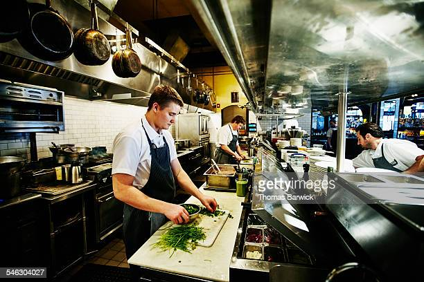 Line cook preparing cilantro in restaurant kitchen