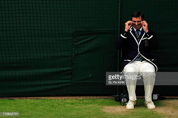 A line judge peers over his glasses as Spain's David Ferrer plays against Argentina's Juan Martin Del Potro during their men's singles quarterfinal...