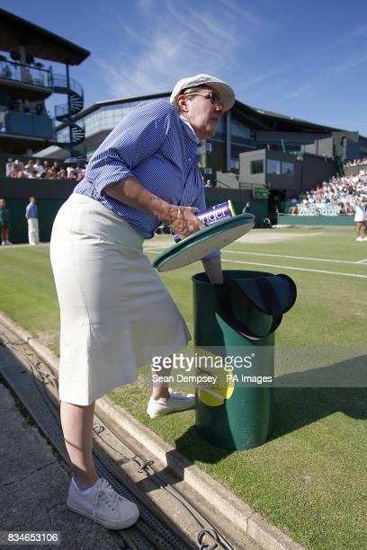 A Line Judge retreives new balls from a slazenger bin