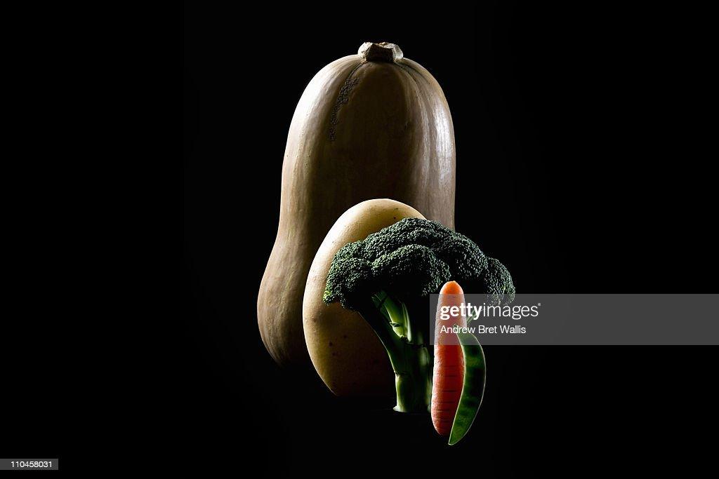 Line of 5 vegetables rim lit against black : Stock Photo