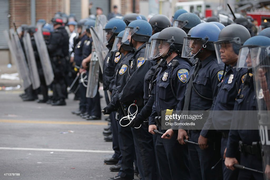 A line of Baltimore Police officers hold their ground at the corner of Pennsylvania and North avenues during violent protests following the funeral...