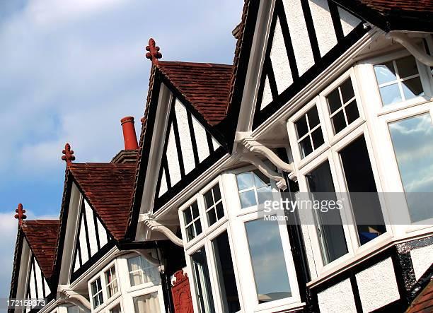 Line of bay windowed cottage homes against blue sky