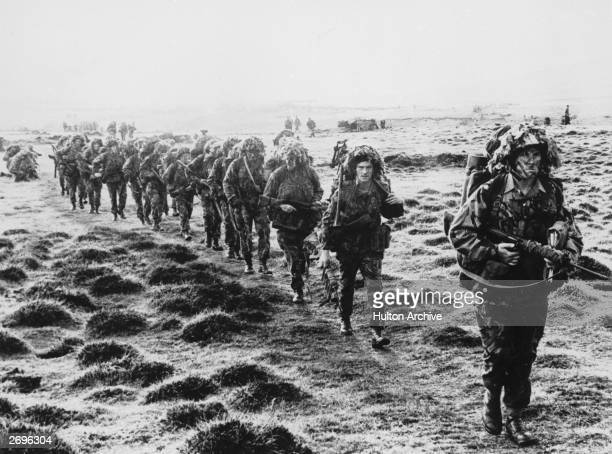 A line of British soldiers in camouflage advancing across East Falkland island for the final attack on Port Stanley during the Falklands War June 1982