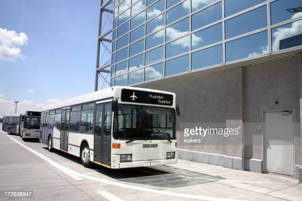 Line of buses by concrete building at airport