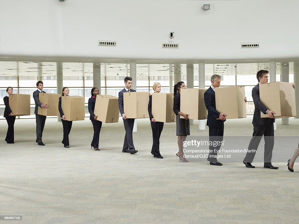 line of business people carrying cardboard boxes : Stock Photo