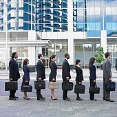 Line of businesspeople holding briefcases outdoors