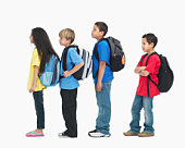 Line of children wearing backpacks