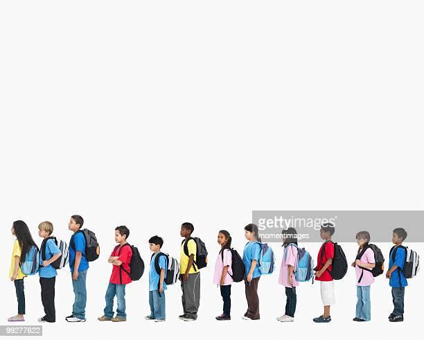 Line of children wearing backpacks