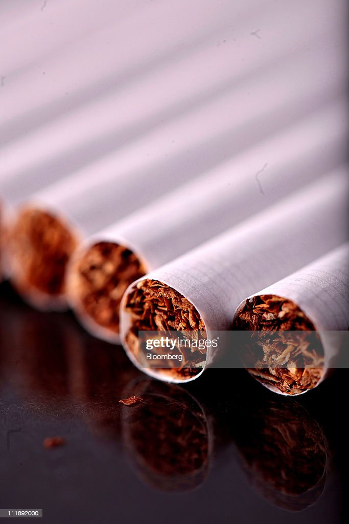 A line of cigarettes sit arranged for a photograph in London, U.K., on Thursday, April 7, 2011. The global market for cigarettes excluding China, which is largely closed to foreign tobacco companies, will probably shrink by 2.5 percent in 2011, BAT Chief Executive Officer Nicandro Durante said Feb. 24. Photographer: Jason Alden/Bloomberg via Getty Images