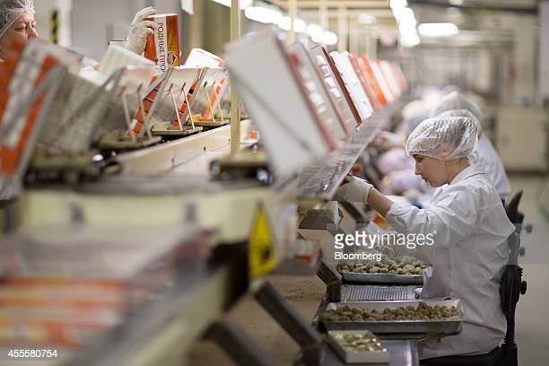 A line of female workers box Rodnye Prostory candies as they move along a conveyor belt at the Rossiya chocolate factory operated by Nestle SA in...