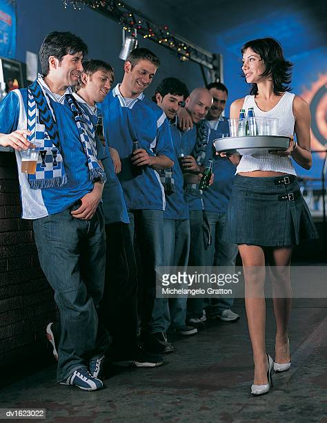 Line of Football Supporters Standing at the Bar Watching a Barmaid Walk by