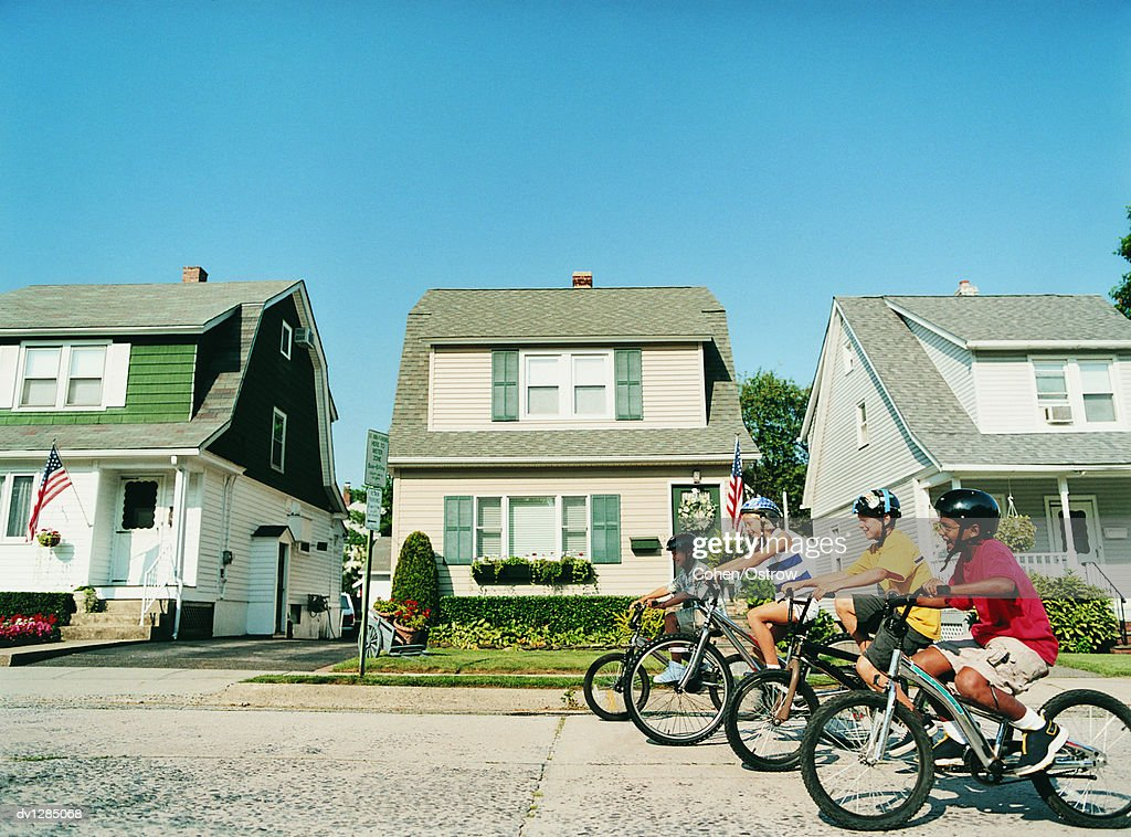 Line of Four Children About To Race Their Mountain Bikes on a Suburban Road in Summer : Stock Photo