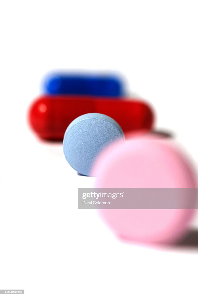 A line of four different pills : Stock Photo