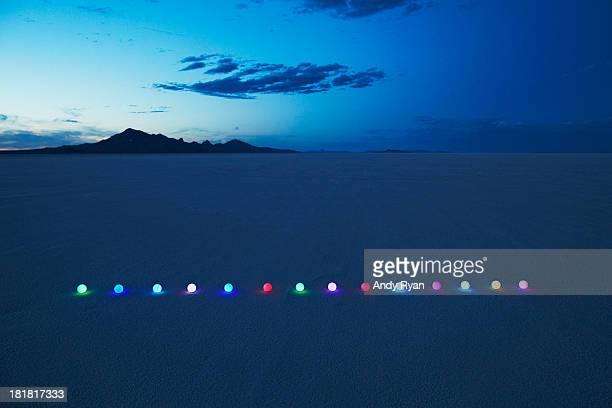 Line of glowing orbs in desert at dusk.