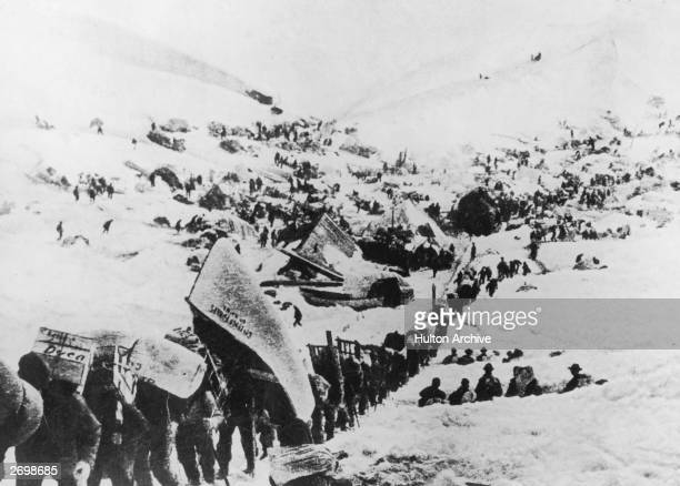A line of gold miners climbing a mountain using a rope during the Klondike gold rush One of the men is carrying a canoe on his back