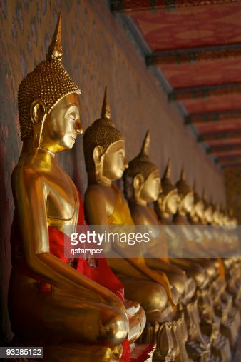 Line of golden Buddha statues in red and orange silk robes