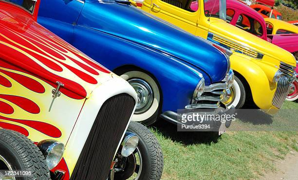 line of hotrod cars in grass at car show