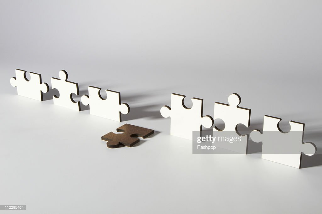 Line of jigsaw pieces with one fallen piece : Stock Photo