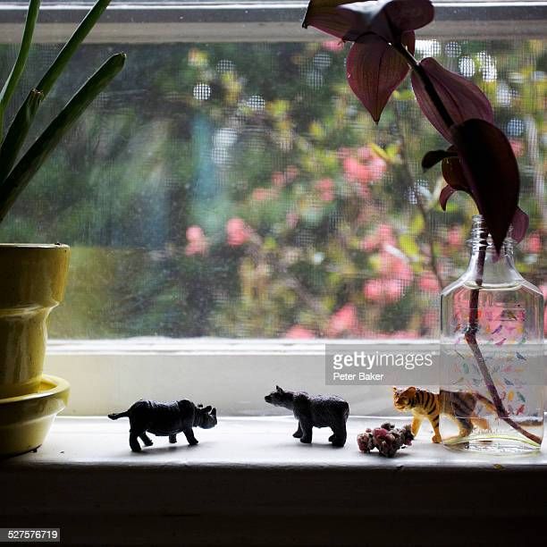 A line of miniature plastic toy animals on a window sill