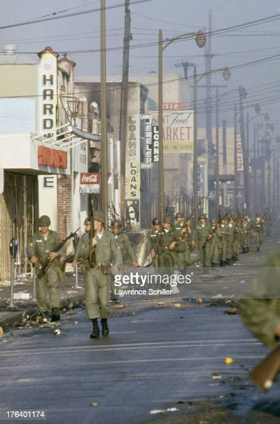 A line of National Guardsmen march past shuttered and burnedout businesses on a street in the Watts neighborhood after the declaration of Marshall...