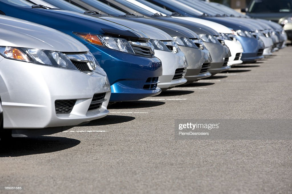 Line of new compact cars at dealership.
