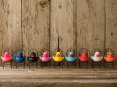 Line of of many different colored rubber ducks sitting on chairs facing towards the camera, scene set in front of old wooden paneling. Concept image of living together, harmony, humanity, social issue