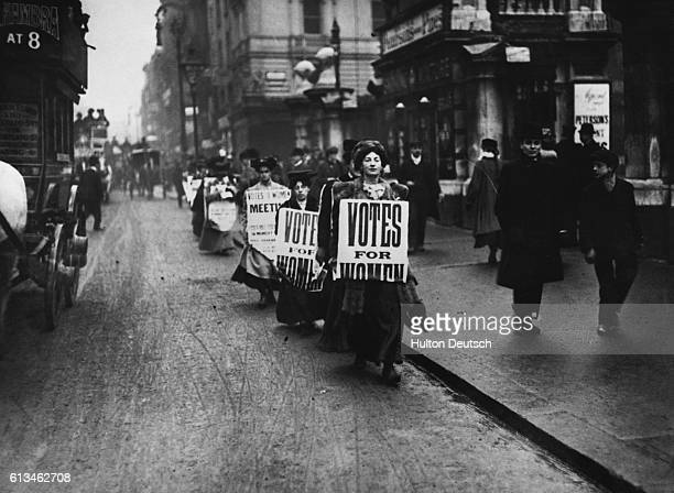 A line of placard holding Suffragettes walk down a London street demonstrating in favour of votes for women 1912