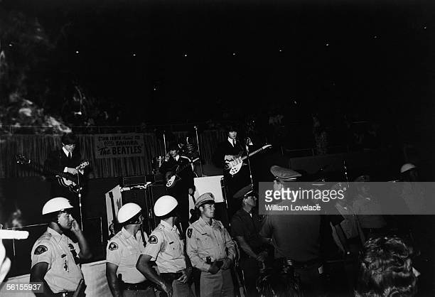 A line of police officers protect the stage as The Beatles prepare to perform at the Convention Hall Las Vegas during the groups tour of America 20th...
