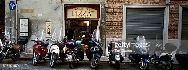 A line of scooters parked in front of a pizzeria in Rome, Italy