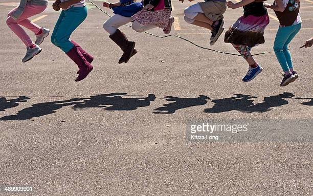 A line of seven kids jumping with one large rope.